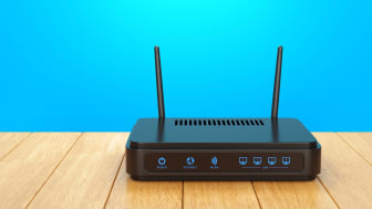Wireless wi-fi router with two antennas on wooden table. High speed internet connection, computer network and telecommunication technology concept. (Wireless wi-fi router with two antennas on