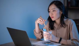 Photo of woman looking at computer and shopping while eating noodles.