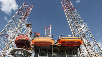 bottom view of an oil platform with two large lifeboats attached to it