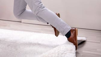 Low Section Of Man Legs Stumbling With A Carpet At Home