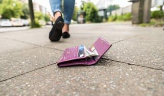 Woman unknowingly drops her purple wallet on a sidewalk