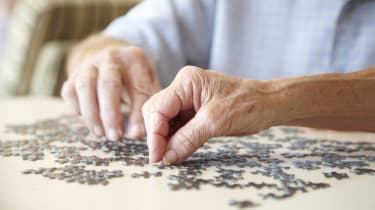 Elderly couple, aged 75-80, looking for pieces of a jigsaw puzzle in a private retirement home