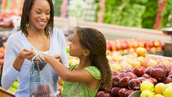 A  mother and daughter shopping in the produce section of a supermarket