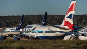 A British Airways jet sits on a tarmac with other large jetliners