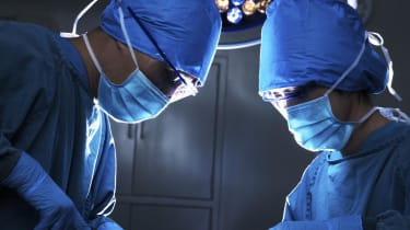 Two surgeons looking down, and concentrating at the operating table