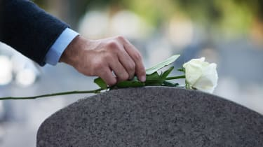 A person laying a flower on a gravestone