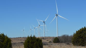 A series of wind turbines generating power on a clear windy day in Oklahoma.