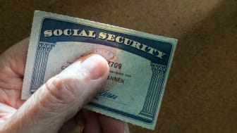 Someone holds up a Social Security card