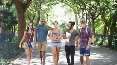 A group of college students walk on campus.