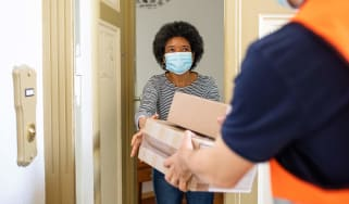 Courier guy delivers parcel to a woman at home during quarantine.