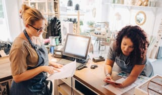 A small business owners goes through a checklist with her partner.