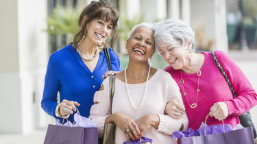 A group of three multi-ethnic senior women in their 60s and 70s shopping together, carrying shopping bags. They are standing on a sidewalk laughing and looking at the camera.