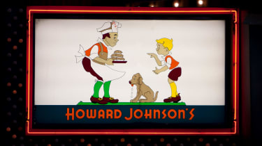"""Howard Johnson's restaurant sign at the famous 1960's restaurant in Times Square New York City. Original logo on sign with neon outline at night."""""""