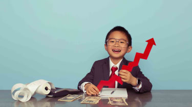 A child dressed up like a businessman holding a model of a stock chart arrow pointing up