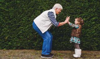 A grandma high-fives her little granddaughter