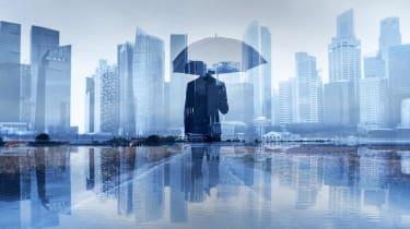 A businessman holds an umbrella.