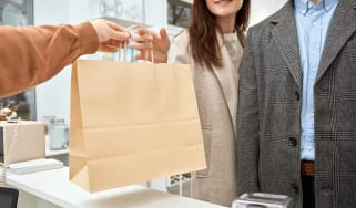Cropped view of adult shopaholic husband and wife buying wear in shopping center on black friday, holding paper bags in hands