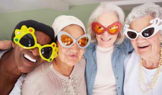 Four senior ladies wear funny glasses and smile.
