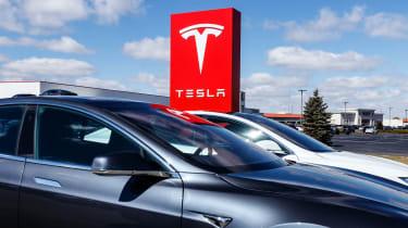 Tesla sedans in front of a Tesla sign
