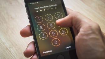 Bangkok, Thaïlande - 12 décembre 2015 : Apple iPhone5s tenu dans une main montrant son écran avec pavé numérique pour entrer le mot de passe.
