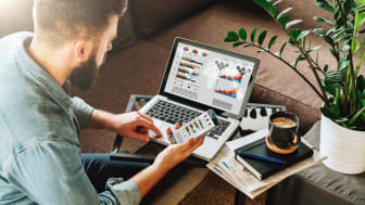 Young man, entrepreneur, freelancer sits at home on couch at coffee table, uses smartphone, working on laptop with graphs, charts, diagrams on screen.Online marketing,education, e-learning. S