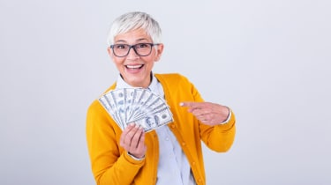 picture of elderly woman holding and point to cash