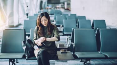 Young businesswoman holding passport and boarding pass on hand, checking wristwatch in airport