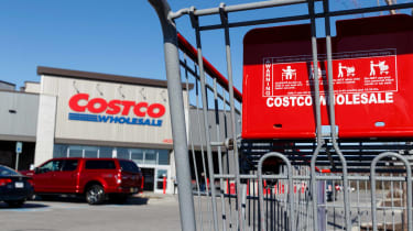 Front of Costco store from parking lot with Costco shopping cart in foreground
