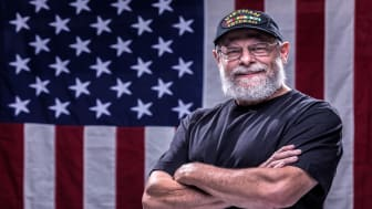 photo of veteran in front of American flag