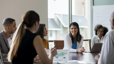 Businesswoman talks with colleagues during weekly meeting.