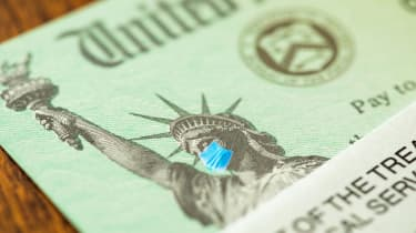 picture of government check with face mask on the Statue of Liberty