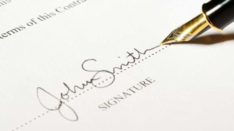 A pen signing on the dotted line of a contract.The signature is fictitious.