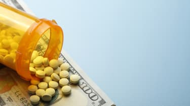 Pills spill out onto a one hundred dollar bill from an open prescription medication bottle. Ample room created by light blue background for copy and text.