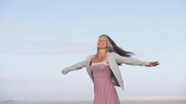 Woman walking with her arms stretched out as if flying