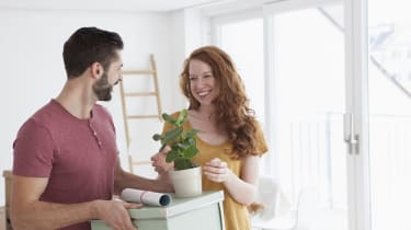 Young couple in new flat with cardboard boxes unpacking boxes