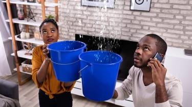 A couple hold buckets under a leak in their living room ceiling.