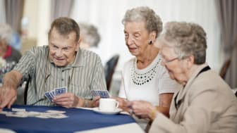 A group of seniors at a nursing home (or retirement center) drinking tea or coffee and playing cards together.