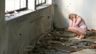 A woman kneels in shock in her flood-ruined house.