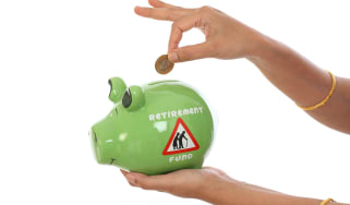 Woman hand inserting coin in a piggy bank against white background