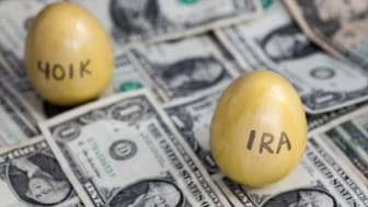 Selective focus on a golden egg identified as IRA, with a second egg labeled 401k in the background.Both are financial mechanisms to save for retirement.The eggs are sitting upon many one dol