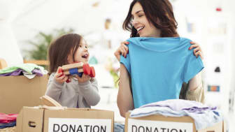 picture of a mother and daughter packing up clothes and toys to donate to charity