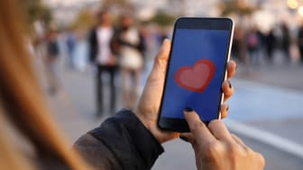 Hand holding smart phone with sending heart