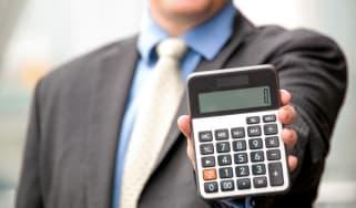 A man holds up a calculator.