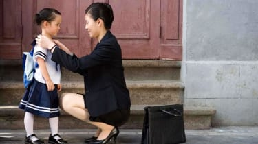 A mom in a business suit and briefcase gets her daughter ready for school.