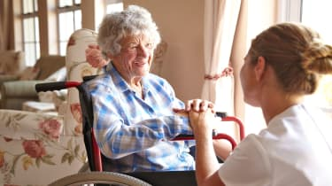 picture of elderly woman in wheelchair talking to nurse in long-term care facility