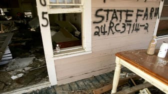 photo of damaged house with insurance information spray painted on it.