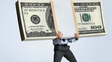 A man in office attire is weighed down by a stack of $100 bills.