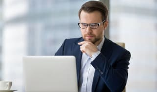 Caucasian man sitting at the table near laptop in the office and looking at the screen. Serious and pensive boss or employee working at his workplace and feeling interest or analyzing results