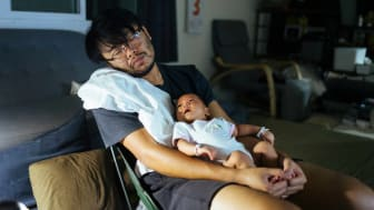 Father sleeping in chair holding infant who is looking up at his face