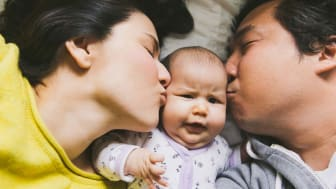 picture of two parents kissing a baby on the cheeks